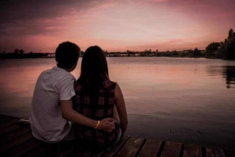 Paar sitzt auf Steg und schaut auf den Sonnenuntergang am See