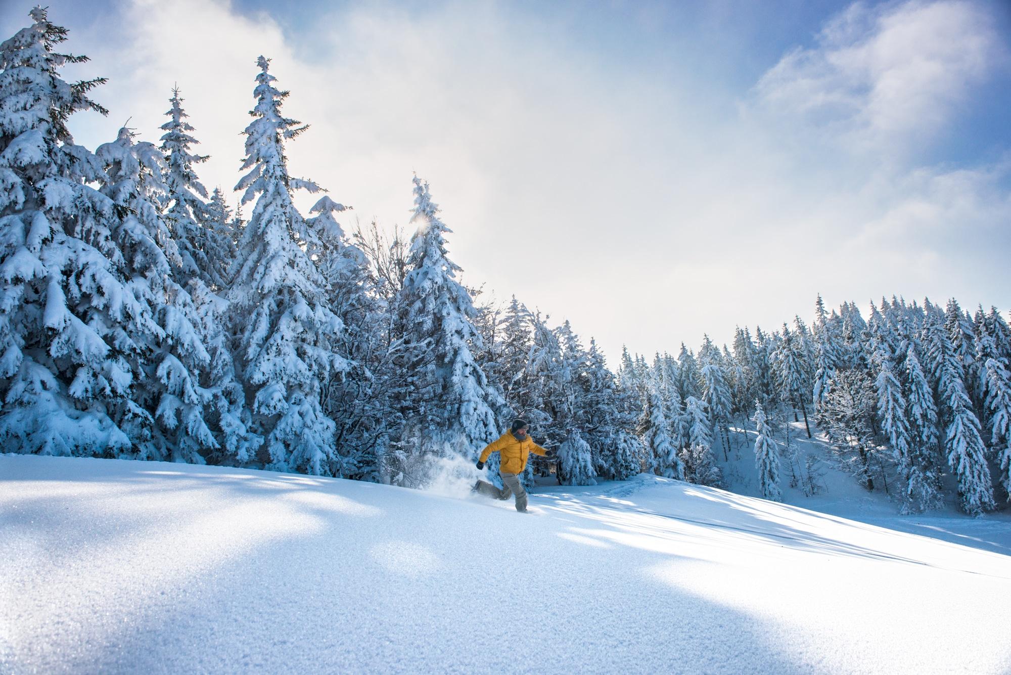 Mann läuft durch hohen Schnee im Schwarzwald