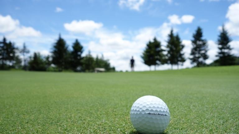 Golfplatz mit Golfball im Vordergrund