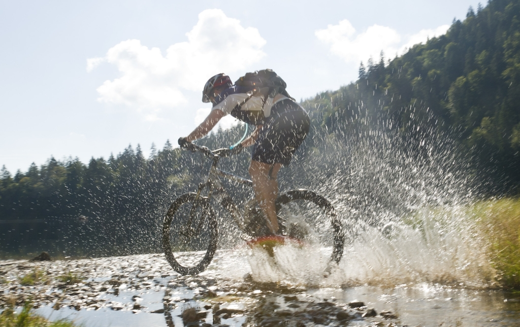 Mountainbiker im Schwarzwald fährt durch Wasser