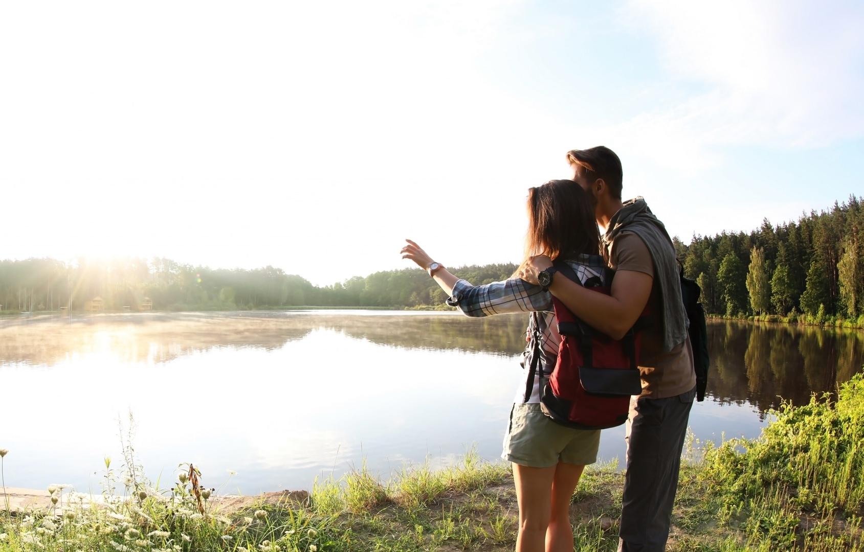 Junges Paar beim Wandern, schaut auf den See