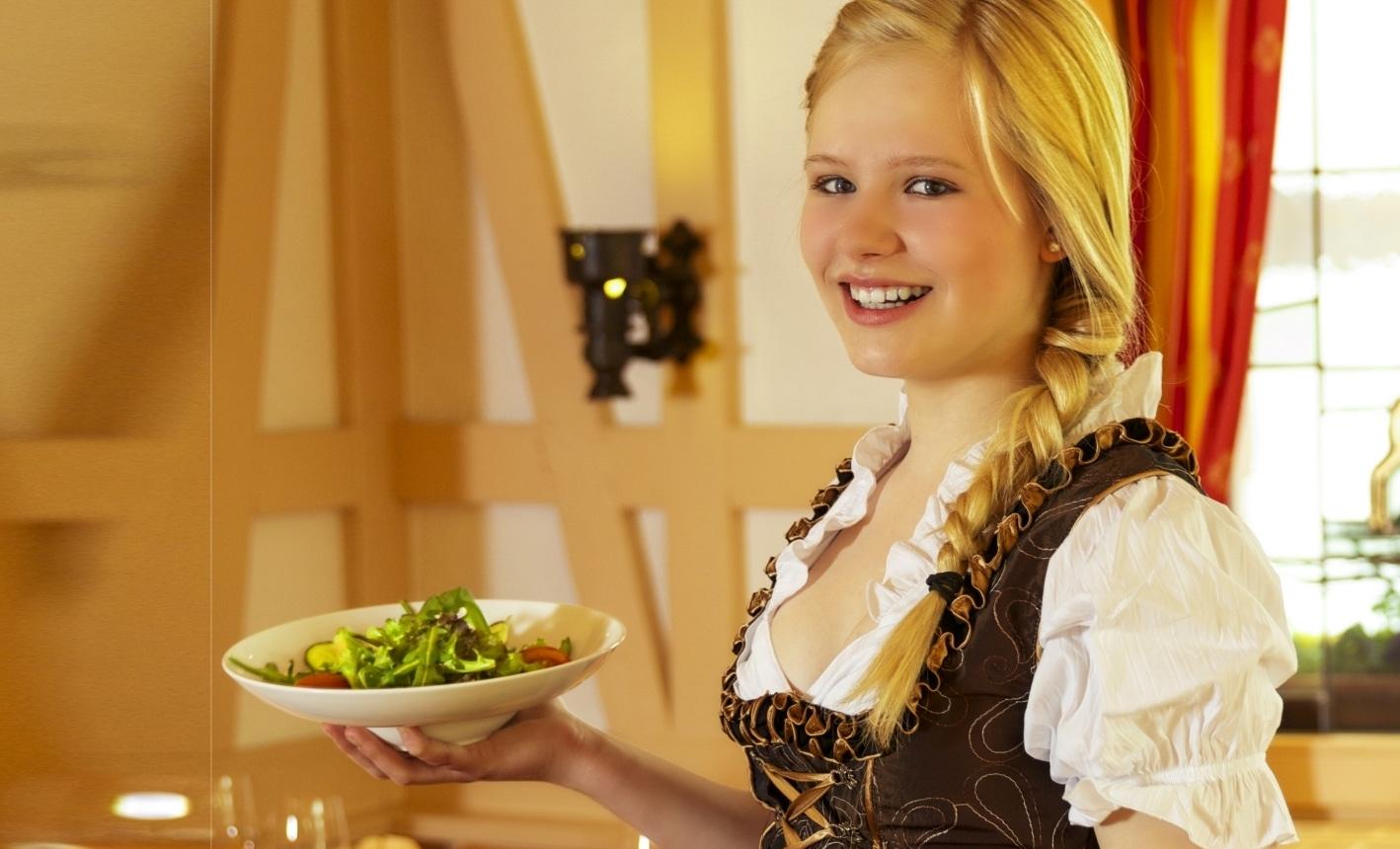 Kellnerin im Dirndl beim Servieren