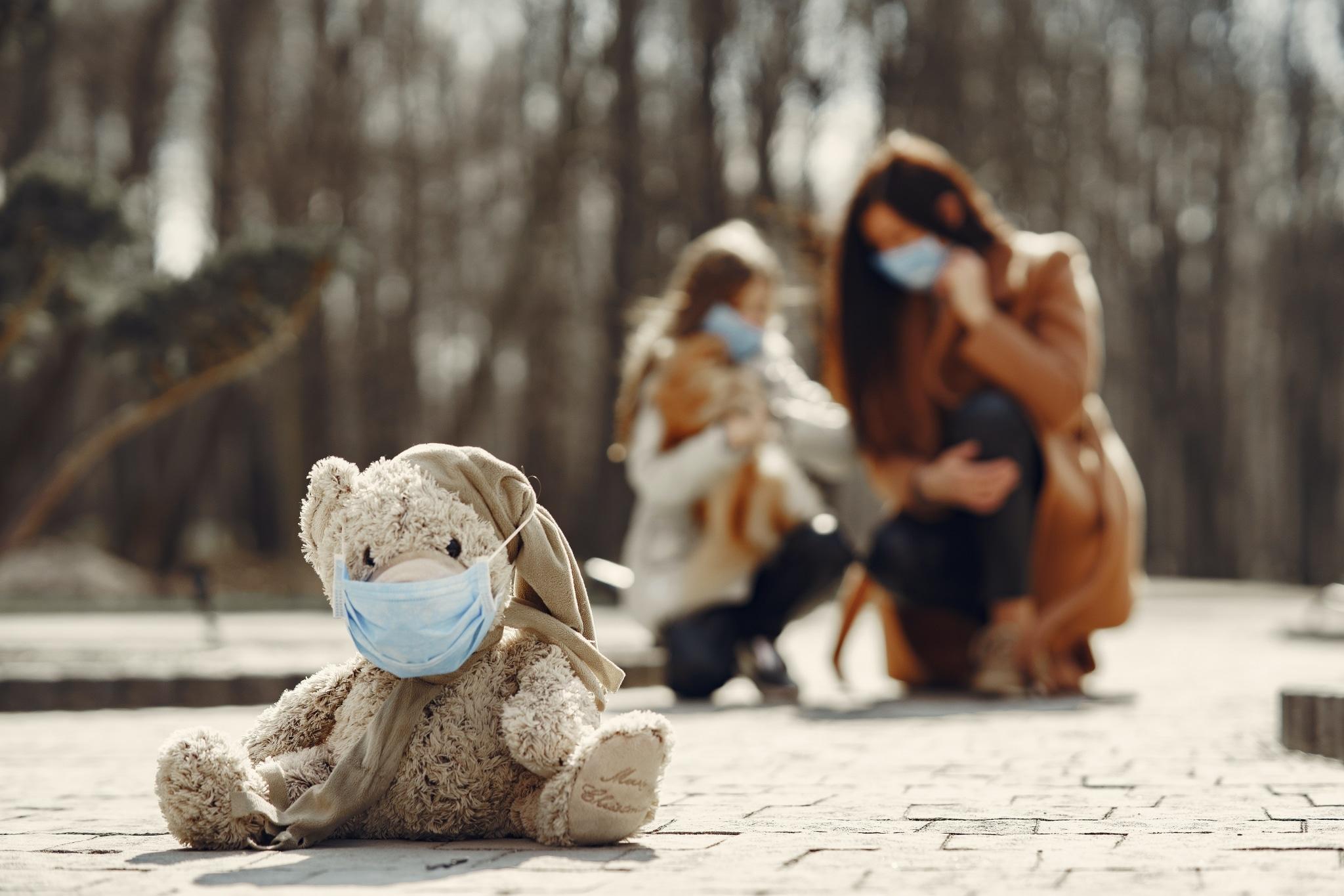 Frau, Kind und Teddy mit Atemschutzmaske